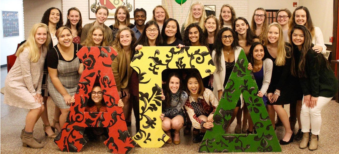 Members of Alpha Gamma Delta sorority pose in front of their letters.